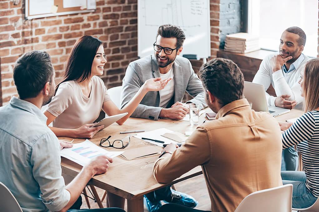 a workforce sitting around a desk discussing strategies
